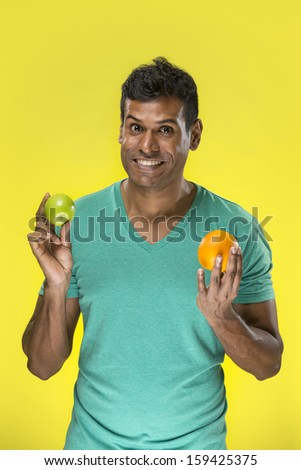Happy Indian man holding fruit on yellow background. Healthy eating concept. Young and fresh Asian male model. - stock photo