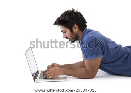 Happy Indian man lying on floor using a laptop PC. Isolated on White Background. - stock photo