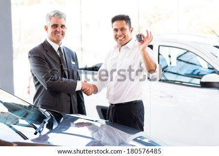 happy indian man showing new car key while handshaking with salesman - stock photo