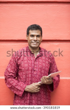 Happy Indian man using tablet computer on street. Traditional indian male wearing a kurta with tablet computer outside. - stock photo