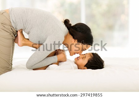 happy indian mother playing with her little boy on bed - stock photo