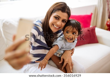 Happy Indian mother taking selfie with little daughter - stock photo