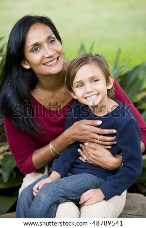Happy Indian mother with cute mixed-race five year old son on lap - stock photo