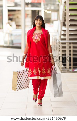 happy indian woman carrying shopping bags walking in mall - stock photo