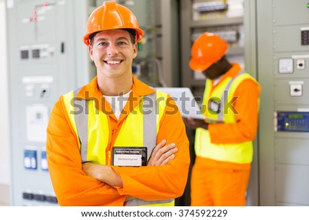 happy industrial engineer with colleague on background in control room - stock photo