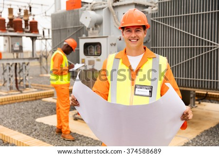 happy industrial engineer working in electric substation - stock photo