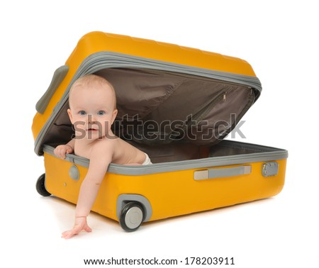Happy infant baby toddler sitting in yellow plastic travel suitcase on wheels getting ready for vacation and looking at the corner isolated on a white background - stock photo