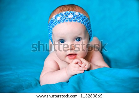 happy infant girl in  blue hat - stock photo