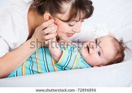 Happy infant smiling and his mother - stock photo