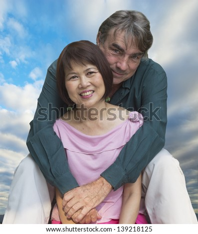 Happy interacial couple hugging with roses - stock photo