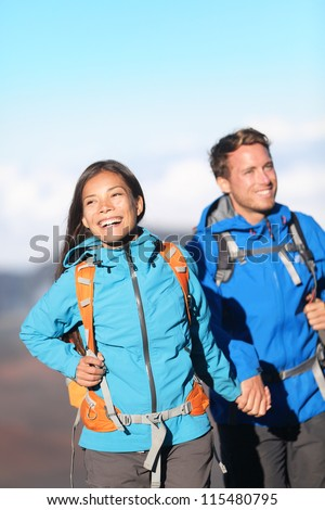 Happy interracial couple hiking holding hands on mountain hike. Sporty young couple walking outside high in mountains. Joyful cheerful Asian girl and Caucasian man hikers. - stock photo