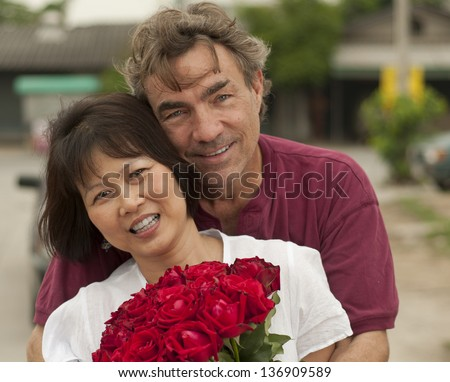 Happy interracial couple hugging with roses - stock photo