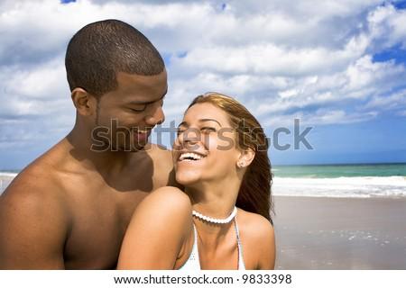 Happy interracial couple on a beach - stock photo