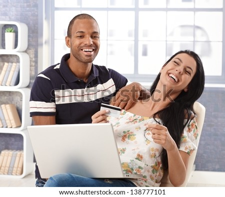 Happy interracial couple shopping online at home, using credit card, laughing. - stock photo