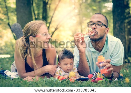 Happy interracial family blowing bubbles retro filter effect instagram filter. Mixed diverse family is enjoying a day in the park. Mother father and mulatto son smiling and picnicking in green park. - stock photo