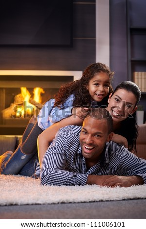 Happy interracial family having fun at home by fireplace, lying on each other's back, laughing. - stock photo
