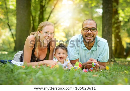 Happy interracial family in enjoying a day in the park - stock photo