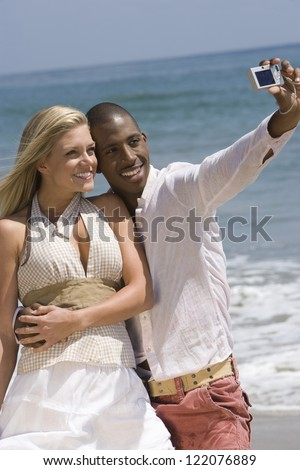 Happy interracial young couple posing for a self portrait photograph on beach