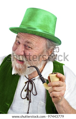 Happy Irish leprechaun with white beard, top hat, green velvet vest, and curved pipe in hand. He raises eyebrows, smiles and tilts head. Isolated on white, vertical layout with copy space. - stock photo