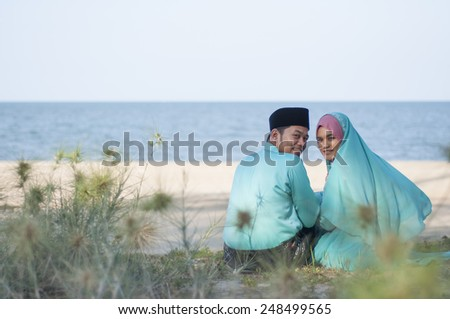 Happy islamic couple posing looking to the camera at the beach - stock photo