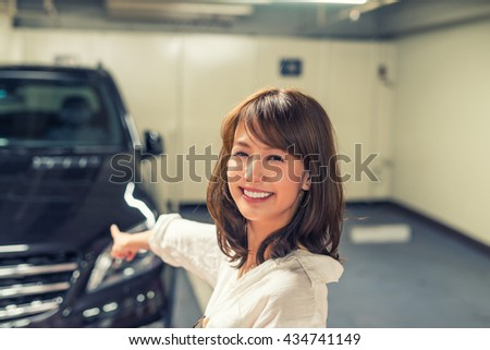 Happy japanese girl showing her brand new car. - stock photo