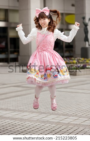 Happy japanese sweet lolita cosplay jumping on a Tokyo sidewalk - stock photo