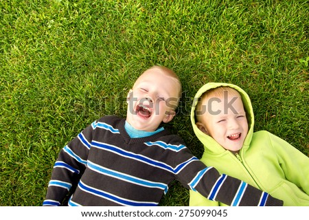 Happy joyful beautiful children (two little caucasian blond boys, brothers) lying on green grass and having fun outdoor, sunny summer day, copy space, horizontal. - stock photo