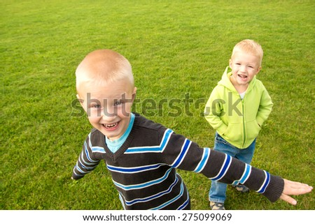 Happy joyful beautiful children (two little caucasian blond boys, brothers) playing on green grass and having fun outdoor, sunny summer day, copy space, horizontal. - stock photo