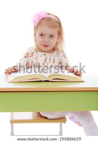 Happy joyful blonde girl is reading a thick book sitting on the table - isolated on white background - stock photo