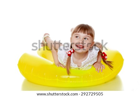 Happy joyful blonde girl with pigtails is on a yellow inflatable round swimming in the water - isolated on white background - stock photo