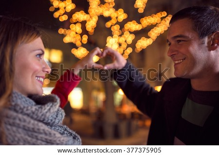 Happy joyful couple on Christmastime at street  with heart sign making by their hands - stock photo