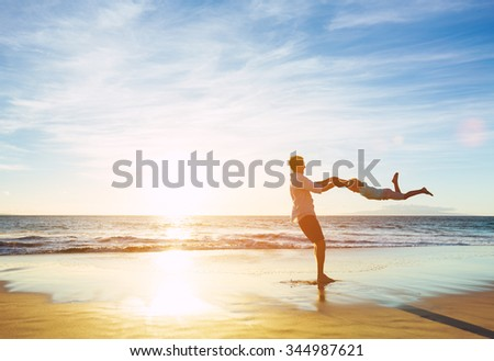 Happy Joyful Father and Son Playing on the Beach at Sunset. Fatherhood Family Concept