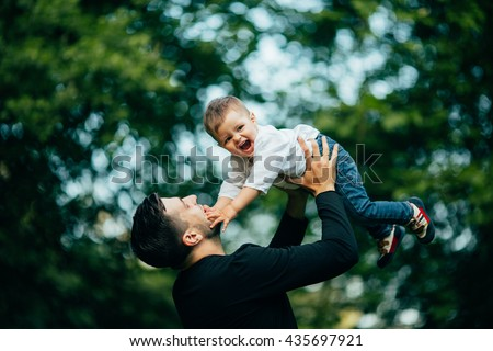 happy joyful father having fun throws up in the air his small child, family, father's day - concept. - stock photo