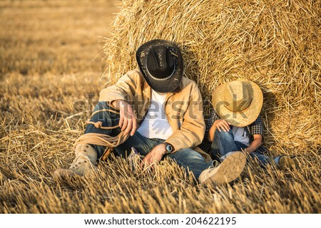 Happy joyful father with a cute son in cowboy hats, family, travel, vacation, father's day - concept. focus on father - stock photo
