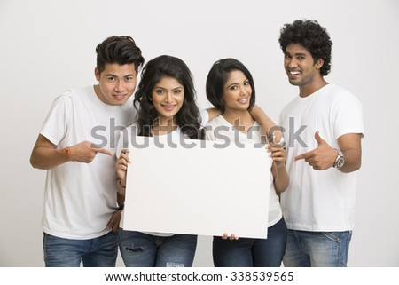 Happy joyful group of friends displaying white boad for your text on white background - stock photo