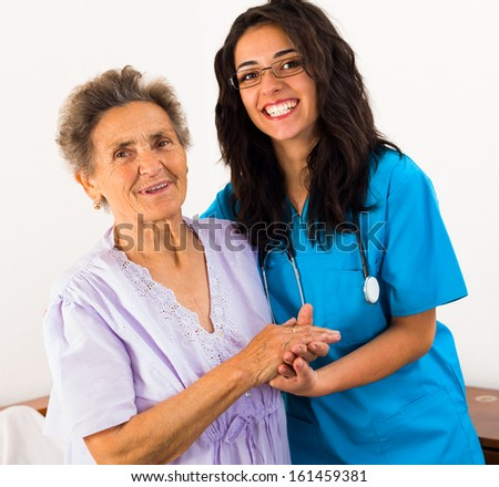 Happy joyful nurses caring for kind elderly patients helping their days in nursing home.