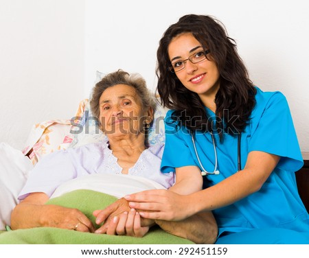 Happy joyful nurses caring for kind elderly patients helping their days in nursing home. - stock photo