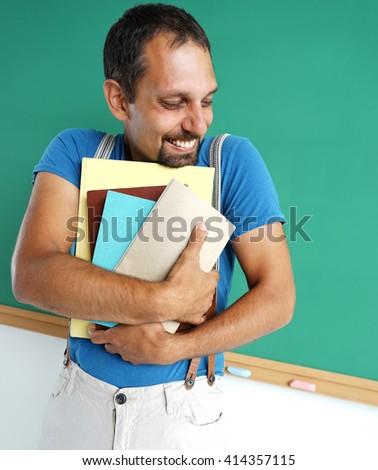 Happy joyful teacher likes to read books. Photo adult teacher near blackboard, education concept - stock photo