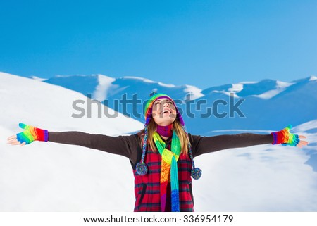 Happy joyful woman with raised hands enjoying beauty of winter nature, spending leisure time in the snowy mountains - stock photo
