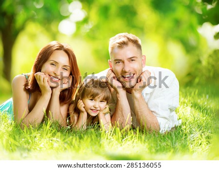 Happy joyful young family father, mother and little daughter having fun outdoors, playing together in summer park. Mom, Dad and kid laughing, lyying on green grass, enjoying nature outside. Sunny day - stock photo