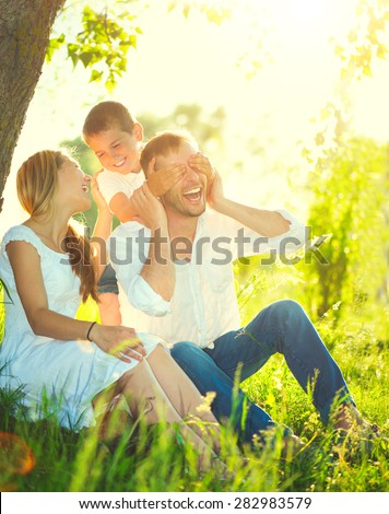 Happy joyful young family father, mother and little son having fun outdoors, playing together in summer park. Mom, Dad and kid laughing and hugging, enjoying nature outside. Sunny day, good mood