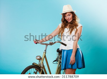 Happy joyful young woman with bike bicycle. Fashionable girl in hat, white shirt and skirt. Summer fashion and recreation. Studio shot. - stock photo
