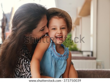 Happy joying kid girl embracing with beautiful mother on summer bright background - stock photo