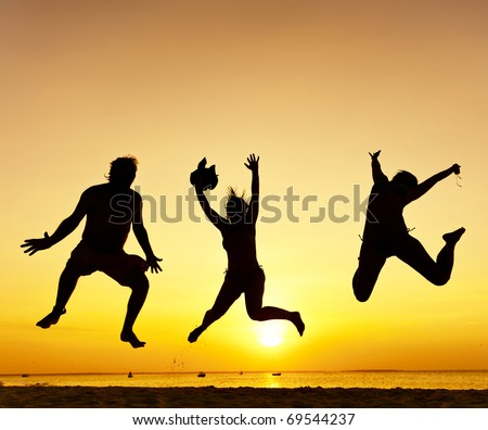 Happy jump during sunset or sunrise while on holiday at the beach. - stock photo