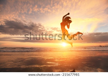 Happy jump sport young woman running on the beach at sunrise, asian - stock photo