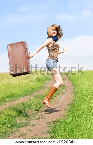 happy jumping girl with a suitcase outdoor