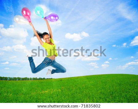 happy jumping young woman with balloons outdoor on a summer day