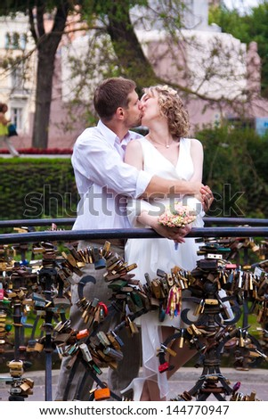 Happy just married couple kissing on the small bridge