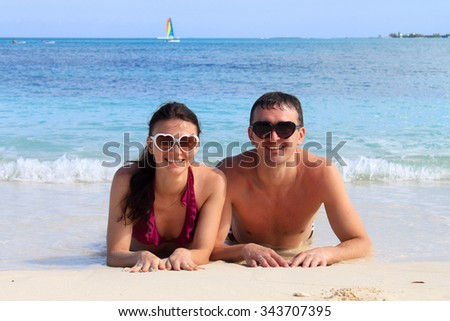 Happy just married couple lay on the beach of the Bahamas, wear heart sunglasses