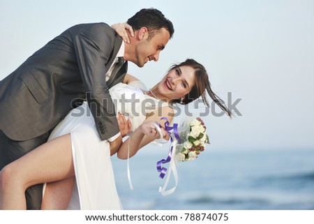 happy just married young couple celebrating and have fun at beautiful beach sunset - stock photo